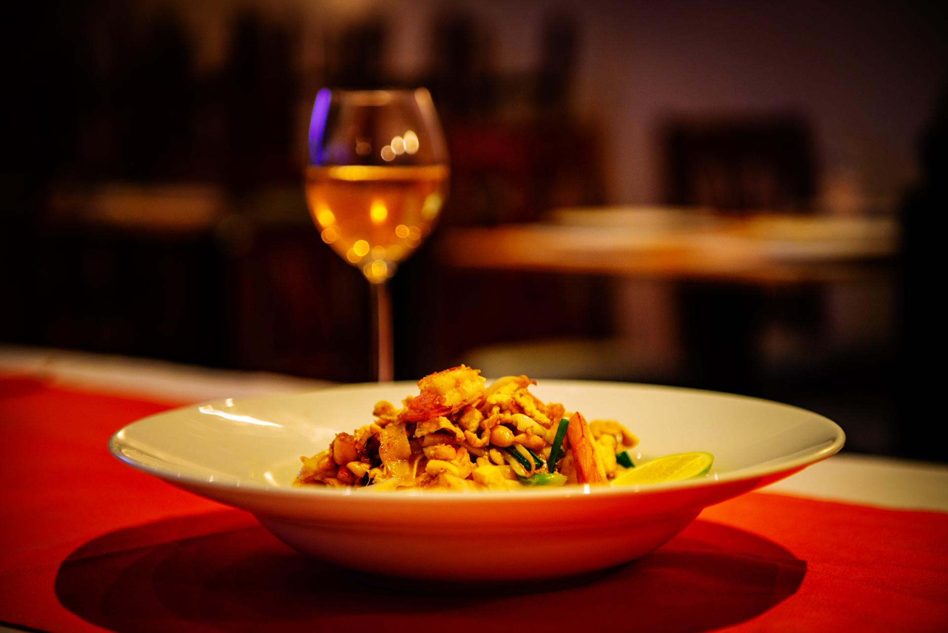 Thailändisches Gericht mit Wein als Deko
